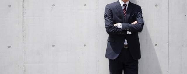 コンクリートの壁の前に腕を組み立つスーツ姿の男性の首から膝までの画像