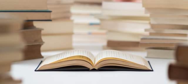 机の奥には多数の本が積まれ、手前に一冊の分厚い本が開いて置かれている