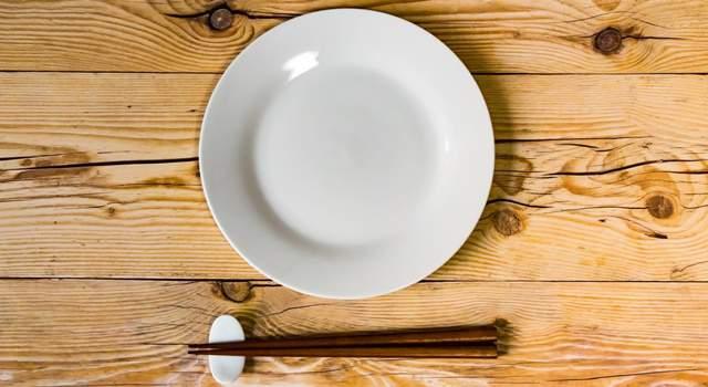 木目調のテーブルに置かれた空の皿と箸