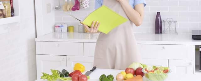 キッチンで食材を前にしてレシピブックを見ながら考え込むエプロン姿の女性