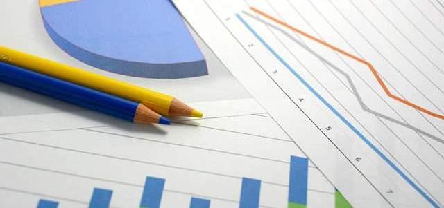 折れ線グラフ、棒グラフ、円グラフがかかれた書類が重なり合う上に青・黄色の色鉛筆が置かれている