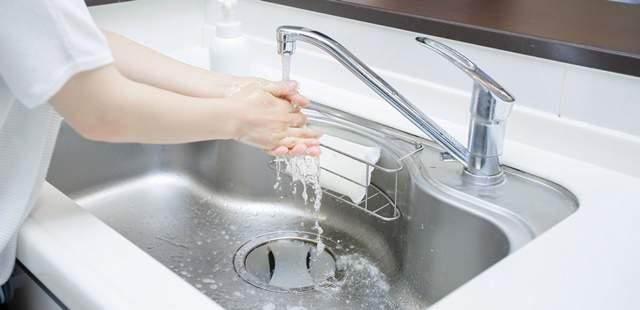 キッチンの流しで手をすすぐ女性の腕から手のアップ