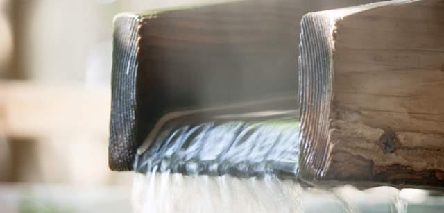 木の注ぎ口からお湯が流れ出るアップの画像