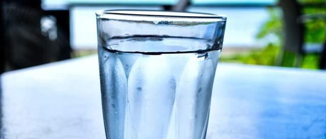 テーブルの上の水が注がれたグラス。全体的に青く、背景が自然っぽいキレイな画像