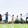 草原で手を繋いでジャンプする3世帯家族
