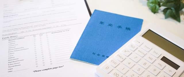 テーブルの上に書類と年金手帳と電卓が置かれている