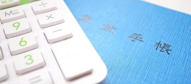 青い年金手帳の上部と白い電卓の右下部が重なり合って写っている