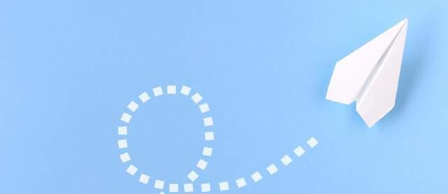 水色の背景に白い紙ヒコーキが軌跡を描いている