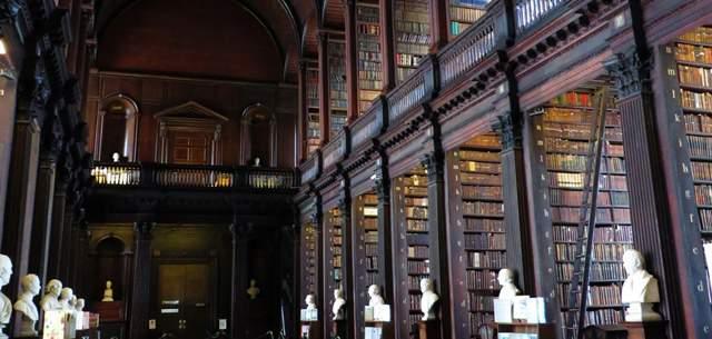 歴史上情緒ある図書館の入口通路。全体的に黒っぽい木目調で、白い石膏像が左右に並んでいる