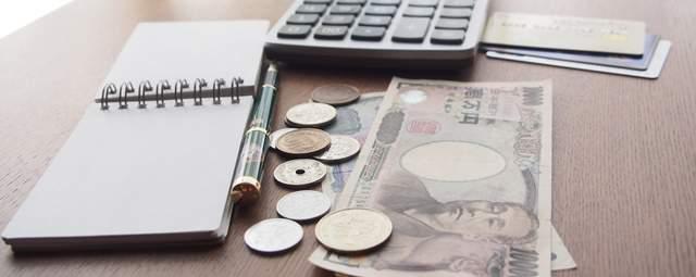 机の上に置かれたお金と電卓とメモ帳