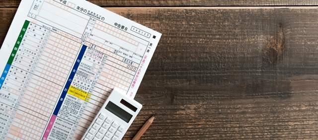 テーブルに置かれた確定申告書と電卓とえんぴつ