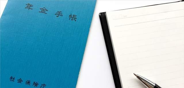 白いテーブルの上に年金手帳が置かれ、その隣に年金手帳と開いたメモ帳の上にボールペンが置かれている