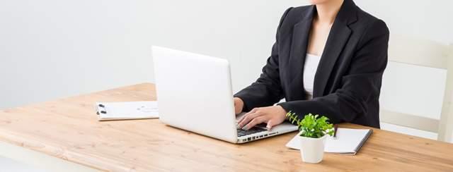 仕事机のでパソコンをいじるスーツ姿の女性