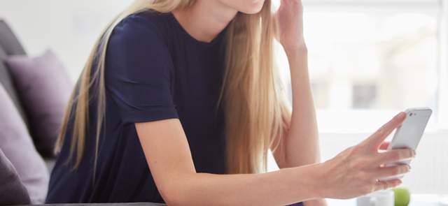 部屋で頬杖を付きながら片手でスマホを持ち眺める青いTシャツ姿の髪の長い外国人女性