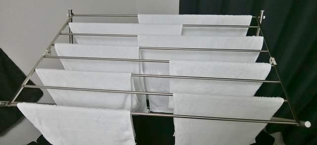 タオル専用の床置き型の金属製の物干しに、白いタオルが何枚もかかっている