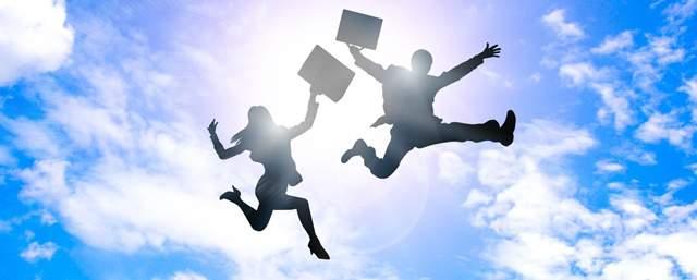 青空をバックに両手を挙げて大きくジャンプするスーツ姿の男女の逆光シルエット