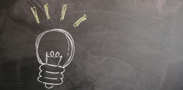 黒板に描かれた電球がピカピカするイラスト