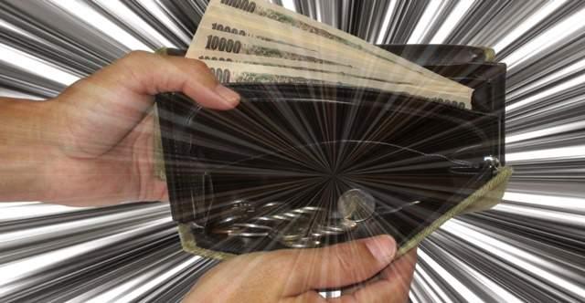 お札と小銭が入った財布を両手で広げている画像