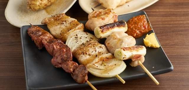 美味しそうな焼き色の焼き鳥3本の盛合せが木のテーブルに置かれている