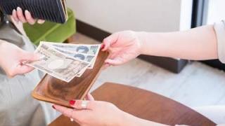 会計でお金の受け渡しをするお客さんと店員さん