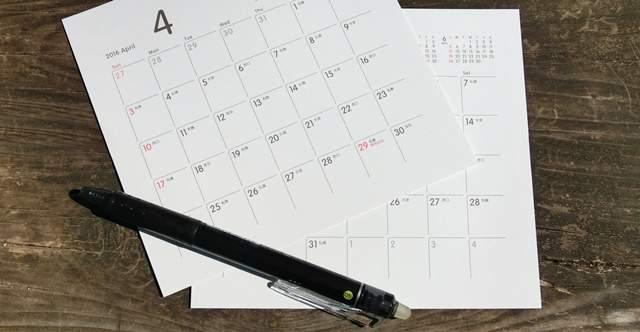 木のテーブルの上に1ヵ月ごとにバラバラの卓上カレンダーの紙数枚とペンが無造作に置かれている
