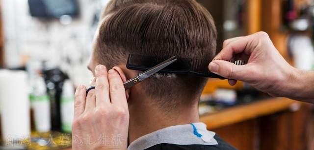 床屋で後ろ髪を刈り上げられている外国人の男性の後ろ姿