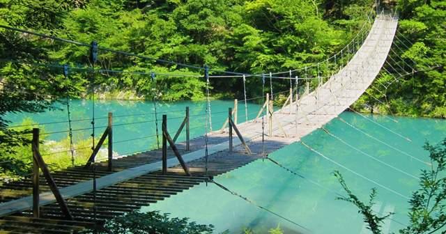 リゾート地の海のような青いキレイな川にかかる簡素で怖い吊り橋