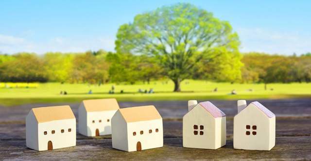 屋外の木のテーブルに置かれた、かわいい家の模型5個が並んでいる