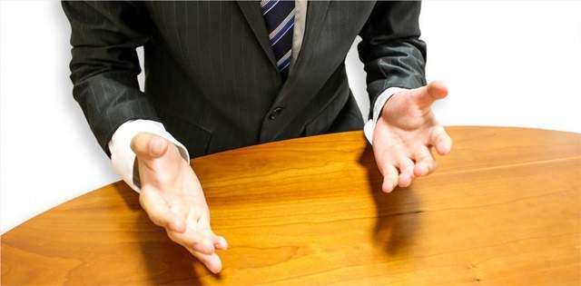 テーブルに両掌を上向きに乗せて何かを説明するスーツ姿の男性