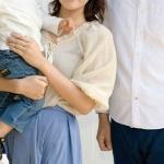 幼子を抱く女性と旦那さんが並んでいる首から下の画像
