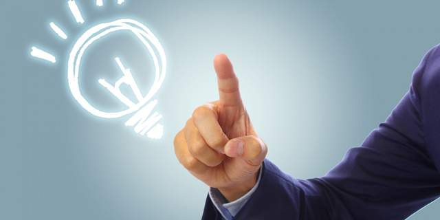 スーツ男性の人差し指の先に電球のマークが浮かんでいる