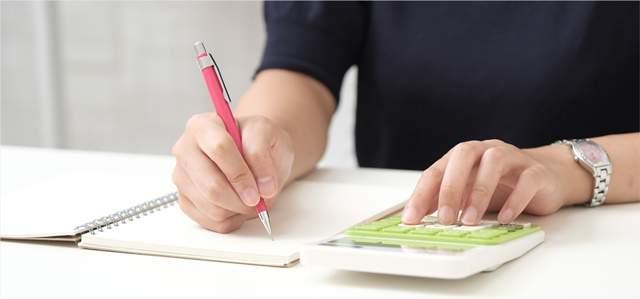 白いテーブルで電卓を打ちながらノートにペンで何かをメモする人の首より下の画像