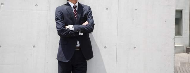コンクリート打ちっ放しの外壁にスーツ姿の男性が寄り掛かり腕を組んでいる、首から下の画像