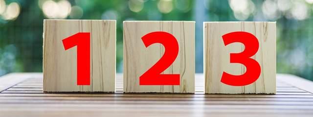 1、2、3とそれぞれ書かれた積み木が、木製のガーデンテーブルに置かれている