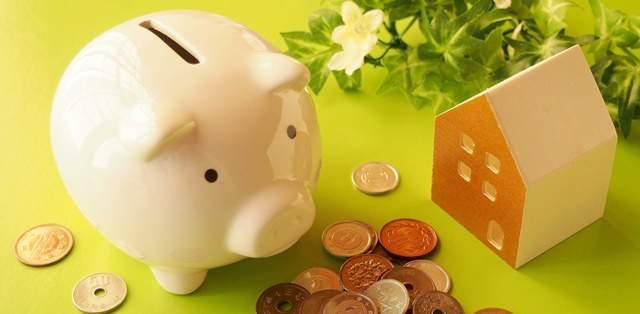 家の模型とブタの貯金箱、小銭が散りばめられている