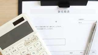 机の上にバインダーに留められた見積書と電卓とボールペンが置いてある