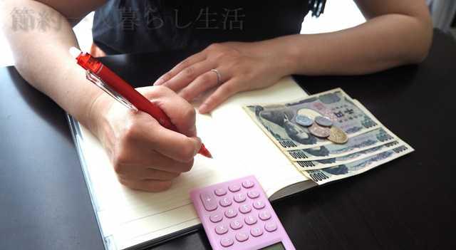 黒い机の上にノートを開き、電卓を見ながらペンで何かを書こうとしている女性。横にはお札が数枚置かれている
