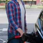 ガソリンスタンドで黒いクルマに給油する、青と赤混じりのチェックシャツ羽織った男性