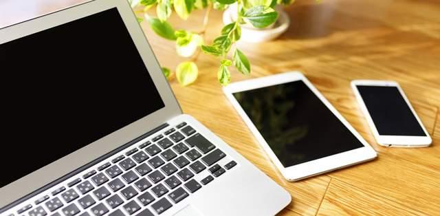 フローリングにノートパソコンとスマホとタブレットが置かれている