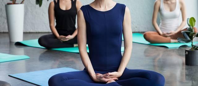 部屋で座禅を組んで瞑想する3人の女性の首から下