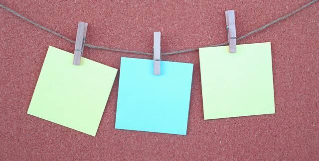 コルクボードの壁にヒモとピンで付箋が3枚留められている