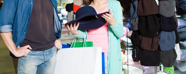 帽子を手に取り品定めする外国人の男女