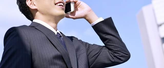 外でスーツ姿で取引先と電話をする若い男性の上半身