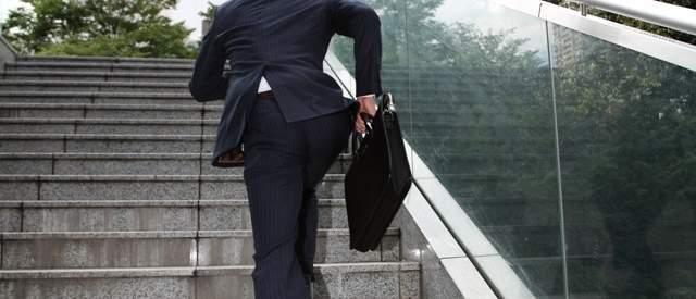 外の階段を駆け上がるスーツを来た男性の後ろ姿