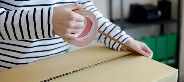 ダンボールにガムテープでフタをする女性