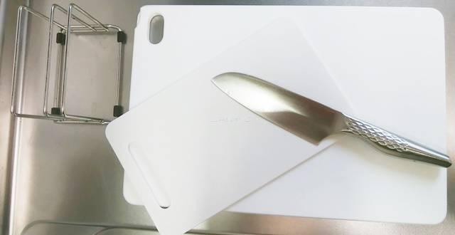 流し台に置かれた大小のまな板とまな板立て、包丁