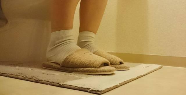 トイレマットが敷かれたトイレの洋式便器にスリッパをはいて座る人の足元