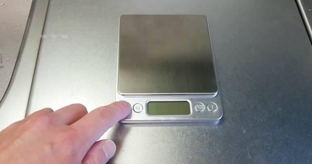 デジタル計りの電源ボタンを押す様子