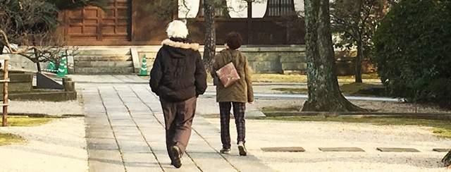神社の石畳を歩く老夫婦の後ろ姿