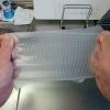 シリコンラップを両手で引っ張って伸ばした図。後ろには洗剤のジョイとまな板が見える